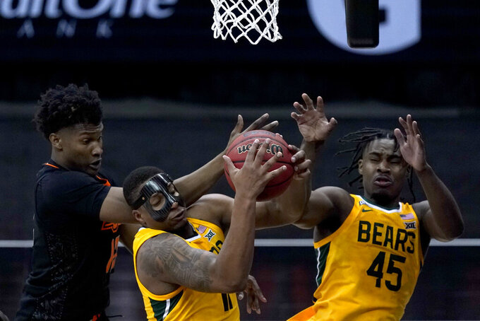 Baylor's Mark Vital, center, beats Oklahoma State's Matthew-Alexander Moncrieffe, left, to a rebound during the first half of an NCAA college basketball game in the semifinals of the Big 12 tournament in Kansas City, Mo., Friday, March 12, 2021. (AP Photo/Charlie Riedel)