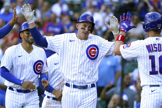 Chicago Cubs' Frank Schwindel, center, celebrates with Patrick Wisdom, right, after hitting a grand slam during the seventh inning of a baseball game against the Pittsburgh Pirates in Chicago, Sunday, Sept. 5, 2021. (AP Photo/Nam Y. Huh)