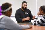 FILE - Baltimore Ravens lineman and math scholar John Urschel teaches a lesson at Dundalk High School to launch Texas Instruments' STEM Behind Cool Careers series in Baltimore, in this Tuesday, July 18, 2017, file photo.  John Urschel has found that a master's degree in mathematics, his stature as an accomplished author and his pending PhD at MIT isn't necessarily enough to sell young students on the benefit of crunching numbers. What really makes him interesting to most kids is that he's a former NFL player who opted to immerse himself in math. (Steve Ruark/AP Images for Texas Instruments, File)