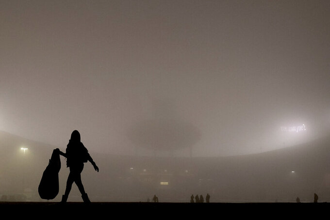 People are shrouded in fog as they clean trash from a parking lot at Arrowhead Stadium after an NFL football game between the Los Angeles Chargers and the Kansas City Chiefs, Sunday, Jan. 3, 2021, in Kansas City, Mo. (AP Photo/Charlie Riedel)
