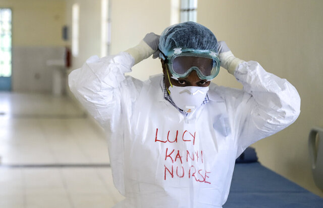 FILE - In this Friday, March 6, 2020 file photo, Kenyan nurse Lucy Kanyi, with her name written on her protective clothing so she can be recognized when wearing it, demonstrates to media the facilities and protective equipment to be used to isolate and treat coronavirus cases, at the infectious disease unit of Kenyatta National Hospital in the capital Nairobi, Kenya. Authorities in Kenya said Friday, March 13, 2020, that a Kenyan woman who recently traveled from the United States via London has tested positive for the new COVID-19 coronavirus, the first case in the East African country. For most people, the new coronavirus causes only mild or moderate symptoms, such as fever and cough. For some, especially older adults and people with existing health problems, it can cause more severe illness, including pneumonia. (AP Photo/Patrick Ngugi, File)