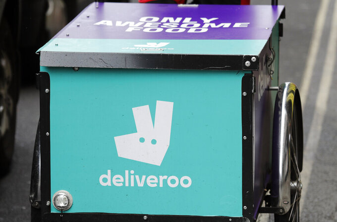 FILE - This Tuesday, July 11, 2017 file photo, shows a deliveroo logo on a bicycle in London. Pizzerias, ride-hailing apps and food delivery services are backing Britain's COVID-19 vaccination drive, offering discounts and even free slices of pizza to persuade young people to roll up their sleeves and get the shot. The program was announced Sunday Aug. 1, 2021 by the Department of Health and Social Care. (AP Photo/Frank Augstein, File)