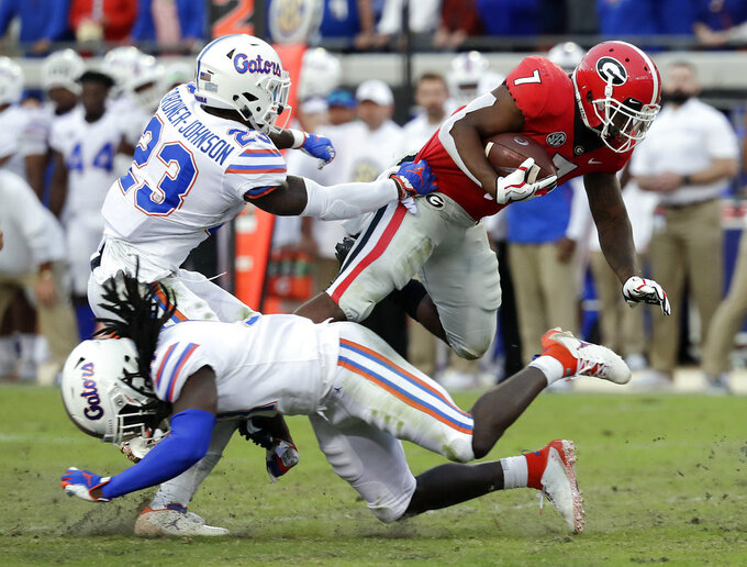 Georgia running back D'Andre Swift (7) runs for yardage over Florida defensive back Chauncey Gardner-Johnson (23) and defensive back Shawn Davis, lower left, during the second half of an NCAA college football game Saturday, Oct. 27, 2018, in Jacksonville, Fla. (AP Photo/John Raoux)