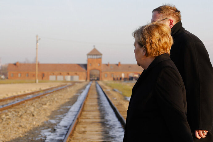 German Chancellor Angela Merkel crosses with Museum director Piotr Cywinski the rail tracks at the ramp in the Nazi death camp of Auschwitz-Birkenau during her visit in Oswiecim, Poland on Friday, Dec. 6, 2019. Merkel visit the former death camp in occasion of the 10th anniversary of the founding of the Auschwitz Foundation. (Photo/Markus Schreiber)