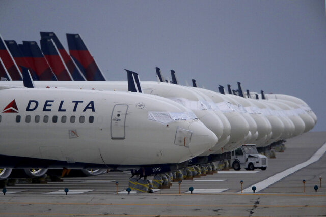 FILE - In this May 14, 2020 file photo, several dozen mothballed Delta Air Lines jets are parked on a closed runway at Kansas City International Airport in Kansas City, Mo. Delta plans to bring back 400 pilots who have been idled because of the travel slump caused by the pandemic. The airline says the pilots will return to regular flying duties by this summer.   (AP Photo/Charlie Riedel, File)