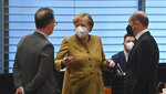 German Chancellor Angela Merkel, center, talks with German Foreign Minister Heiko Maas, left, and German Finance Minister and Vice-Chancellor Olaf Scholz prior to the weekly cabinet meeting at the Chancellery  in Berlin, Germany, Tuesday April 13, 2021. (John MacDougall/AP via Pool)