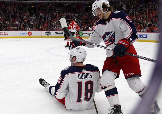 Columbus Blue Jackets center Pierre-Luc Dubois (18) gets a pat on the head from left wing Artemi Panarin (9) after he fell to the ice following a goal against the Chicago Blackhawks during the first period of an NHL hockey game Saturday, Feb. 16, 2019, in Chicago. (AP Photo/Matt Marton)