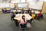 Masked students sit in their classroom on the first day of school at Enrique S. Camarena Elementary School, Wednesday, July 21, 2021, in Chula Vista, Calif. The school is among the first in the state to start the 2021-22 school year with full-day, in-person learning. (AP Photo/Denis Poroy)