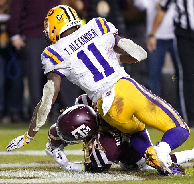 Texas A&M wide receiver Kendrick Rogers, bottom, catches a pass in the end zone for a touchdown as LSU cornerback Terrence Alexander (11) defends during overtime of an NCAA college football game Saturday, Nov. 24, 2018, in College Station, Texas. Texas A&M won 74-72 in seven overtimes. (AP Photo/David J. Phillip)