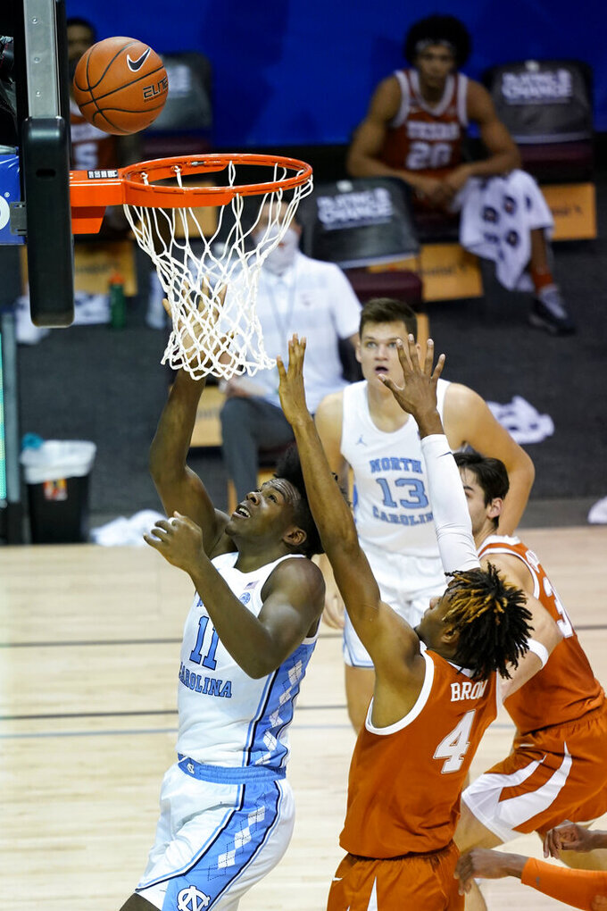North Carolina forward Day'Ron Sharpe (11) shoots a basket past Texas forward Greg Brown (4) in the first half of an NCAA college basketball game for the championship of the Maui Invitational, Wednesday, Dec. 2, 2020, in Asheville, N.C. (AP Photo/Kathy Kmonicek)