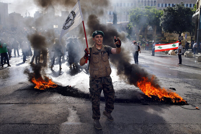 A retired Lebanese soldier chants slogans while holding an army flag, during a protest in Beirut, Lebanon, Monday, May 20, 2019, as the government faces a looming fiscal crisis. Over one hundred protesters gathered Monday in downtown Beirut shouting