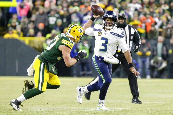 Seattle Seahawks' Russell Wilson scrambles during the first half of an NFL divisional playoff football game against the Green Bay Packers Sunday, Jan. 12, 2020, in Green Bay, Wis. (AP Photo/Mike Roemer)