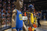 In this Friday, Oct. 11, 2019, photo, a shopper reach holds a basketball near statues of NBA players Stephen Curry of the Golden State Warriors, left, and Lebron James of the Los Angeles Lakers holding Chinese flags in the entrance of an NBA merchandise store Beijing. When Houston Rockets' general manager Daryl Morey tweeted last week in support of anti-government protests in Hong Kong, everything changed for NBA fans in China. A new chant flooded Chinese sports forums: