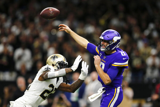 Minnesota Vikings quarterback Kirk Cousins (8) passes under pressure from New Orleans Saints defensive back Chauncey Gardner-Johnson (22) in the first half of an NFL wild-card playoff football game, Sunday, Jan. 5, 2020, in New Orleans. (AP Photo/Brett Duke)