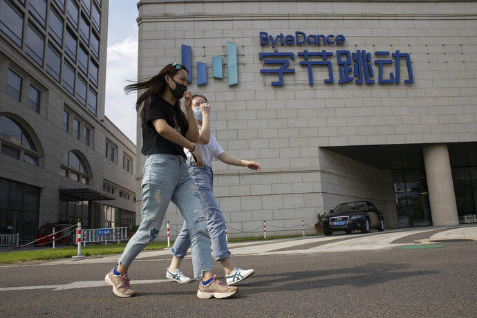 Women wearing masks to prevent the spread of the coronavirus chat as they pass by the ByteDance headquarters in Beijing, China on Friday, Aug. 7, 2020. President Donald Trump on Thursday ordered a sweeping but unspecified ban on dealings with the Chinese owners of consumer apps TikTok and WeChat, although it remains unclear if he has the legal authority to actually ban the apps from the U.S. TikTok is owned by Chinese company ByteDance. (AP Photo/Ng Han Guan)