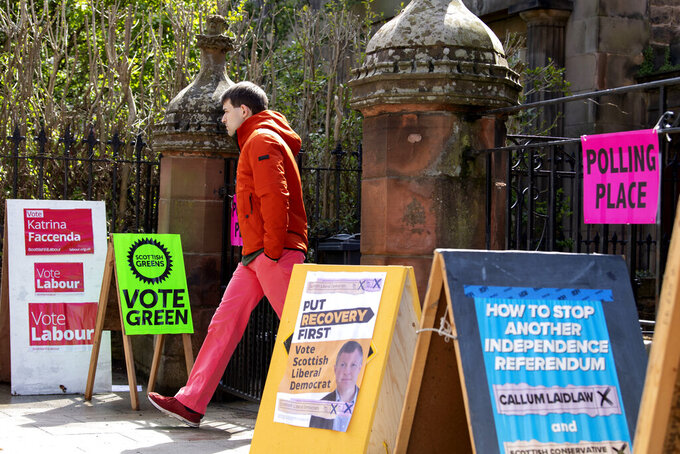 A voter leaves a polling station in Edinburgh, Scotland, Thursday May 6, 2021. Polling stations across Britain have opened in what are considered to be the biggest-ever set of elections outside a general election. At stake are governments for Scotland and Wales, big city mayors, including for London and Manchester, as well as thousands of council members, police commissioners and other local authorities. (Lesley Martin/PA via AP)