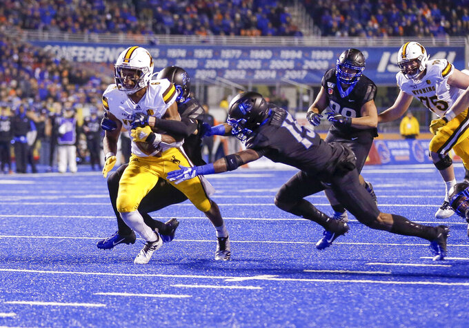Wyoming running back Xazavian Valladay, left, is wrapped up by a Boise State defender as Boise State cornerback Jalen Walker, right, dives in to help during the first half of an NCAA college football game Saturday, Nov. 9, 2019, in Boise, Idaho. (AP Photo/Steve Conner)