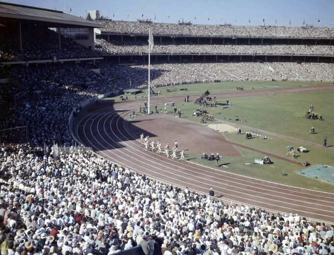 FILE - In this Nov. 22, 1956, file photo, a general view shows crowds and athletes in the Olympic Stadium, in Melbourne, Australia, during the opening ceremony of XVI Olympic Games. An Australian push to host the 2032 Olympics was elevated overnight to the status of preferred bid, and the people of Brisbane and southeast Queensland state woke up to the news Thursday, Feb. 25, 2021. (AP Photo, File)