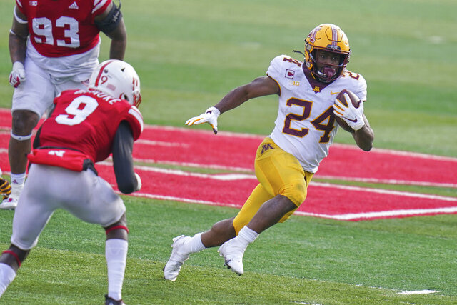Minnesota running back Mohamed Ibrahim (24) carries the ball away from Nebraska safety Marquel Dismuke (9), during the second half of an NCAA college football game in Lincoln, Neb., Saturday, Dec. 12, 2020. Minnesota won 24-17. (AP Photo/Nati Harnik)