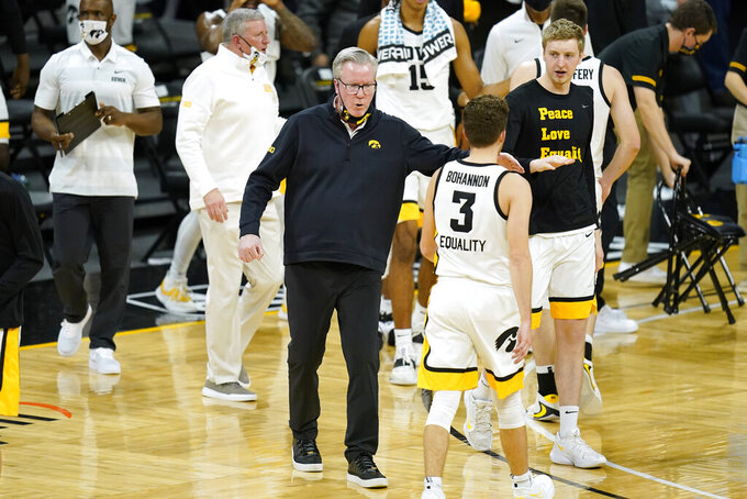 Iowa head coach Fran McCaffery, center, celebrates with guard Jordan Bohannon (3) during the first half of an NCAA college basketball game against Nebraska, Thursday, March 4, 2021, in Iowa City, Iowa. (AP Photo/Charlie Neibergall)