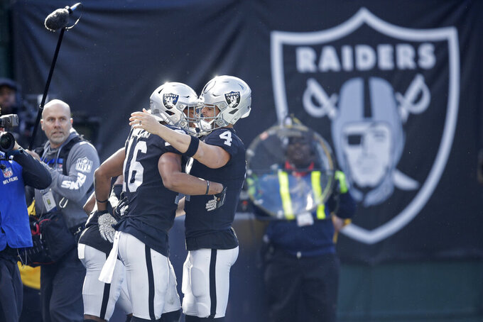 Oakland Raiders wide receiver Tyrell Williams (16) is greeted by quarterback Derek Carr after scoring a touchdown during the first half of an NFL football game against the Jacksonville Jaguars in Oakland, Calif., Sunday, Dec. 15, 2019. (AP Photo/Ben Margot)