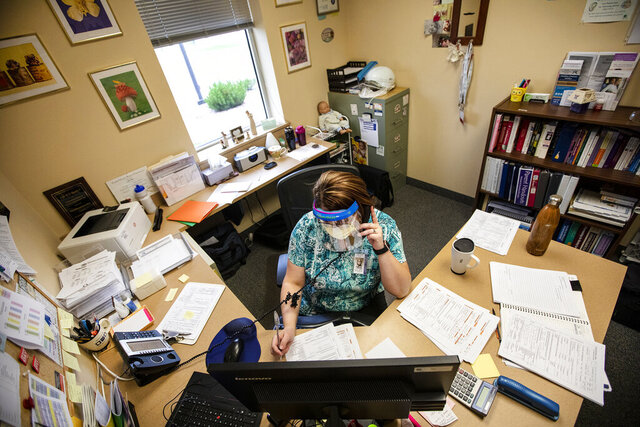 Public Health Nurse Joli Carr asks a series of questions to someone who has tested positive for the coronavirus while conducting a contact tracing phone call on July 24, 2020, at Campbell County Public Health in Gillette, Wyo. (Mike Moore/Gillette News Record via AP)