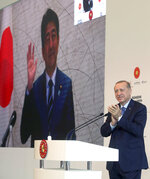 In this photo provided by the Turkish Presidency, Turkey's President Recep Tayyip Erdogan applauds Japanese Prime Minister Shinzo Abe via video link, during the inauguration ceremony for Basaksehir Pine and Sakura City Hospital, in Istanbul, Thursday, May 21, 2020. Abe has called for international cooperation against the new coronavirus, saying any drug or vaccine developed against the virus must be made