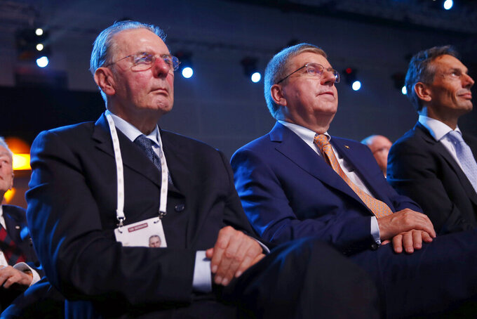 FILE - In this Friday, July 31, 2015 file photo, Honorary President of the International Olympic Committee (IOC) Jacques Rogge, left, sits along with IOC President Thomas Bach, at the 128th IOC session in Kuala Lumpur, Malaysia. The International Olympic Committee on Sunday, Aug. 29, 2021 says Jacques Rogge who led the organization as president for 12 years, has died. He was 79. (AP Photo/Vincent Thian, file)