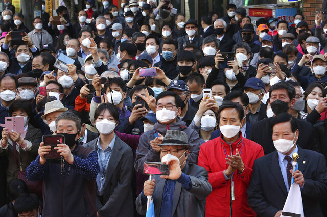 People wearing face masks to help protect against the spread of the new coronavirus listen to a speech of the main opposition United Future Party's candidate Hwang Kyo-ahn during his campaign for the upcoming parliamentary elections in Seoul, South Korea, Monday, April 13, 2020. The elections will be held on April 15 about 14,300 polling stations at all over the nation to pick lawmakers. (AP Photo/Ahn Young-joon)