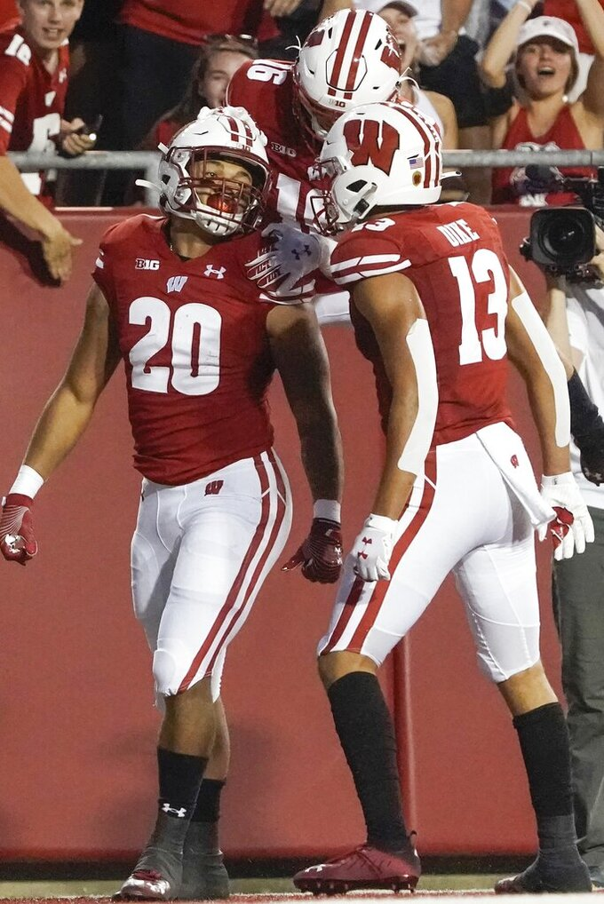 Wisconsin's Isaac Guerendo is congratulated after his 82-yard touchdown run during the first half of an NCAA college football game against Eastern Michigan Saturday, Sept. 11, 2021, in Madison, Wis. (AP Photo/Morry Gash)