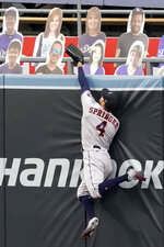 Houston Astros right fielder George Springer leaps but misses the ball for a two-run home run by Los Angeles Dodgers' Mookie Betts during the fifth inning of a baseball game in Los Angeles, Sunday, Sept. 13, 2020. (AP Photo/Alex Gallardo)