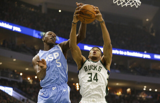 Milwaukee Bucks' Giannis Antetokounmpo (34) fights for a rebound against Minnesota Timberwolves' Gorgui Dieng during the first half of an NBA basketball game Wednesday, Jan. 1, 2020, in Milwaukee. (AP Photo/Jeffrey Phelps)