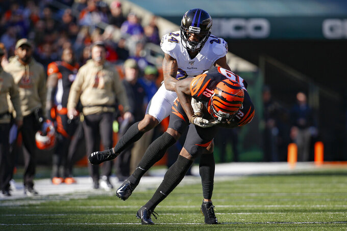 Baltimore Ravens cornerback Brandon Carr (24) tackles Cincinnati Bengals wide receiver Auden Tate (19) during the first half of NFL football game, Sunday, Nov. 10, 2019, in Cincinnati. (AP Photo/Frank Victores)