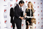 Los Angeles FC soccer player Carlos Vela shows his Major League Soccer Most Valuable Player trophy to his son, Romeo, as his wife, Saioa, looks on Monday, Nov. 4, 2019, in Los Angeles.  (AP Photo/Chris Carlson)