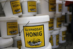 Plastic buckets with contaminated honey are piled up during a demonstration of beekeepers against the use of Glyphosate-based herbicides in farming in Berlin, Germany, Wednesday, Jan. 15, 2020. (AP Photo/Markus Schreiber)