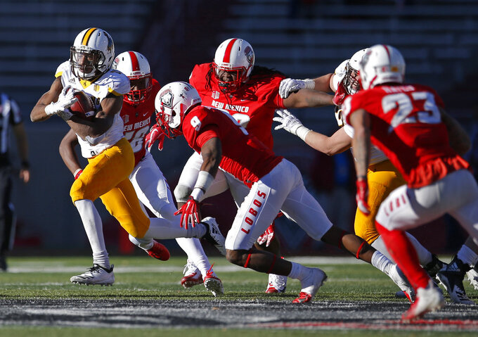 Wyoming running back Xazavian Valladay, far left, breaks away from the New Mexico defense during the second half of an NCAA college football game in Albuquerque, N.M., Saturday, Nov. 24, 2018. Wyoming won 31-3. (AP Photo/Andres Leighton)