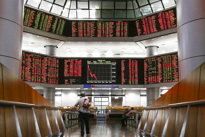 An investor stands in front of stock trading boards at a private stock market gallery in Kuala Lumpur, Malaysia, Thursday, May 2, 2019. Asian stocks were mixed on Thursday after the U.S. Federal Reserve kept its benchmark interest rate intact and steered clear of suggesting that a cut was possible this year. Trading was light as markets in Japan and mainland China were closed. (AP Photo/Annice Lyn)