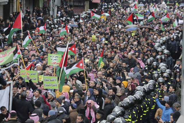 Protesters carry Jordanian and Palestinian flags and slogans during a protest against the Middle East peace plan proposed by U.S. President Donald Trump, in the center of Amman, Jordan, Friday, Jan. 31, 2020. (AP Photo/Raad Adayleh)