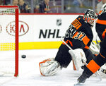 The puck shot by Washington Capitals' Tom Wilson, not pictured, gets past Philadelphia Flyers goalie Brian Elliott for a goal during the first period of an NHL hockey game Wednesday, March 6, 2019, in Philadelphia. (AP Photo/Tom Mihalek)
