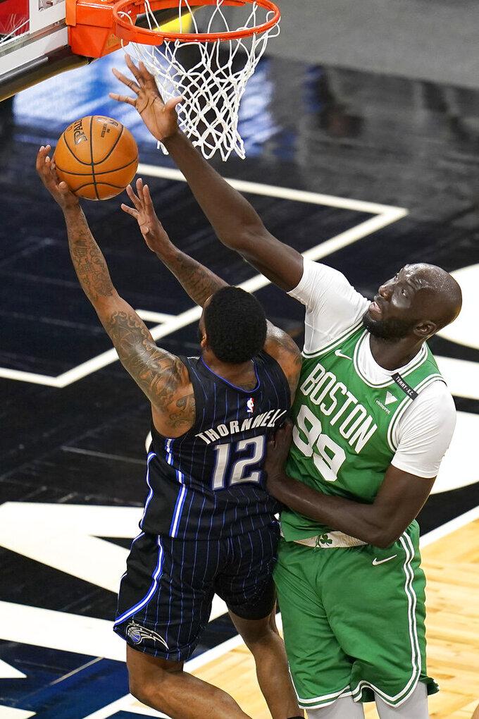 Boston Celtics center Tacko Fall (99) blocks a shot attempt by Orlando Magic guar Sindarius Thornwell (12) during the second half of an NBA basketball game, Wednesday, May 5, 2021, in Orlando, Fla. (AP Photo/John Raoux)