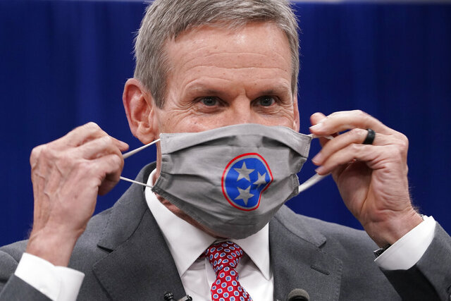 Tennessee Gov. Bill Lee puts on his mask during a break in the state budget hearings Tuesday, Nov. 10, 2020, in Nashville, Tenn. According to a Vanderbilt University School of Medicine study released Tuesday, Tennessee counties that have not required wearing masks in public are on average seeing COVID-19 death rates double or more compared with those that instituted mandates. Lee has opposed a statewide mask mandate, stressing personal responsibility. He has instead allowed counties to decide whether to require masks. (AP Photo/Mark Humphrey)
