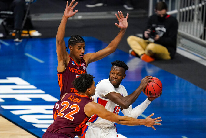 Florida forward Osayi Osifo (15) is trapped by Virginia Tech Hokies forward Keve Aluma (22) and forward David N'Guessan (5) in the first half of a first round game in the NCAA men's college basketball tournament at Hinkle Fieldhouse in Indianapolis, Friday, March 19, 2021. (AP Photo/Michael Conroy)