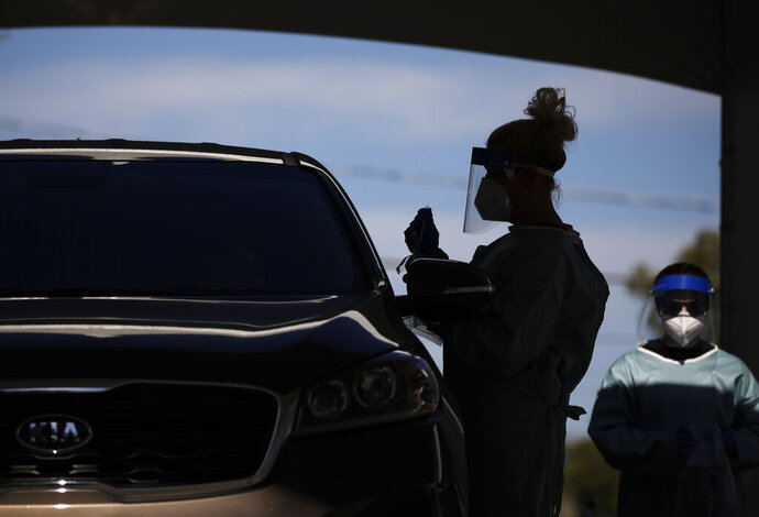 FILE - In this July 10, 2020, file photo healthcare workers test patients in their cars at a drive-thru coronavirus testing site in Las Vegas. (AP Photo/John Locher, File)