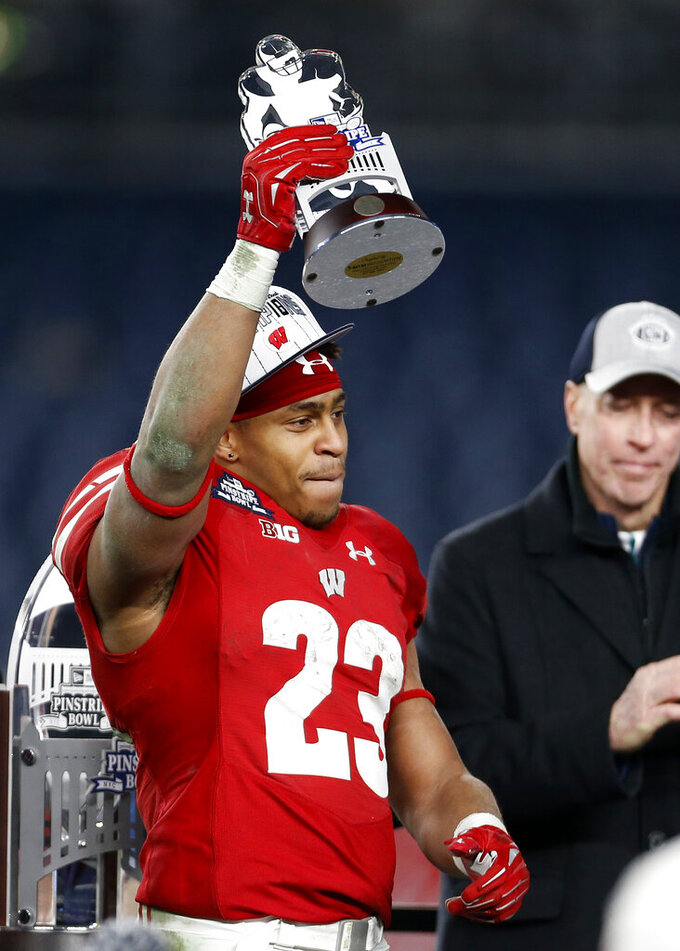 Wisconsin running back Jonathan Taylor holds the MVP Trophy after the team's Pinstripe Bowl NCAA college football game against Miami on Thursday, Dec. 27, 2018, in New York. Wisconsin defeated Miami 35-3. (AP Photo/Adam Hunger)