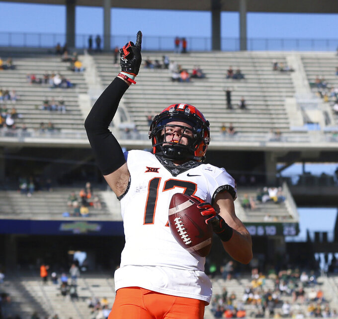 Oklahoma State wide receiver Dillon Stoner points skyward after scoring against Baylor in the first half of an NCAA college football game, Saturday, Dec. 12, 2020, in Waco, Texas. (Rod Aydelotte/Waco Tribune-Herald via AP)