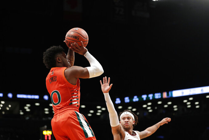 Miami's Chris Lykes (0) shoots over Temple's Alani Moore II during the first half of an NCAA college basketball game at Barclays Center, Tuesday, Dec. 17, 2019, in New York. (AP Photo/Michael Owens)