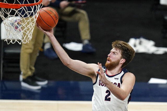 FILE - In this Dec. 2, 2020, file photo, Gonzaga's Drew Timme goes to the basket during the second half of the team's NCAA college basketball game against West Virginia in Indianapolis. Coach Mark Few of top-ranked Gonzaga says the suspension of basketball activities for the past two weeks because of the coronavirus pandemic has ''not helped us in any way, shape or form.″ (AP Photo/Darron Cummings, File)