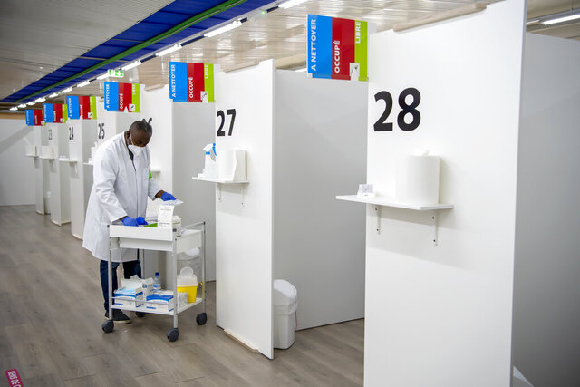 A nurse prepares to administer a Pfizer/BioNTech vaccine to a couple at the at the m3 Sanitrade vaccination center in Geneva, Switzerland, on Wednesday, Jan. 6, 2021. The canton of Geneva launches its vaccination campaign against Covid-19. (Martial Trezzini/Keystone via AP)