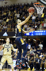 UNC-Greensboro guard Francis Alonso, right, drives the ball to the basket past Wofford guard Storm Murphy (5) in the second half of an NCAA college basketball game for the Southern Conference tournament championship, Monday, March 11, 2019, in Asheville, N.C. (AP Photo/Kathy Kmonicek)