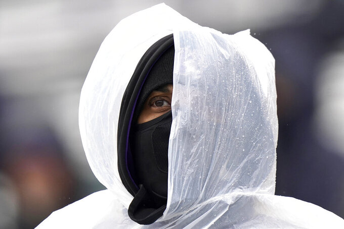 A Northwestern fan covers up for the rain as he watches an NCAA college football game between Illinois and Northwestern during the second half in Evanston, Ill., Saturday, Dec. 12, 2020. Northwestern won 28-10. (AP Photo/Nam Y. Huh)